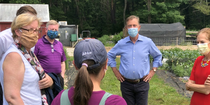Governor Lamont speaks with people at a farm in Ledyard